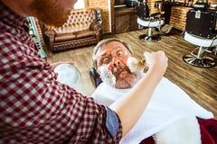 Santa Claus som rakar hans personliga barberare Arkivfoton