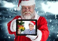 Santa Claus som rymmer en digital minnestavla med fotoet av mannen Arkivfoton