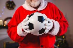Santa Claus som rymmer en fotboll Royaltyfri Fotografi