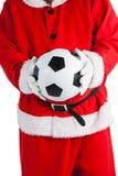 Santa Claus som rymmer en fotboll Arkivbild