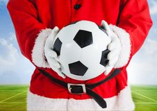 Santa Claus som rymmer en fotboll Royaltyfria Bilder