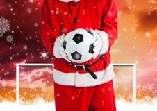 Santa Claus som rymmer en fotbollboll Arkivbild