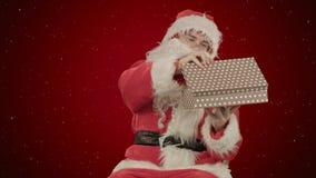 Santa Claus som rymmer en gåva i hans hand på röd bakgrund med snö Arkivfoto