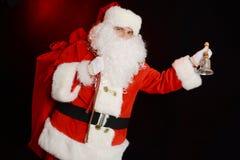 Santa Claus som rymmer en påse med gåvor och ringer en klocka royaltyfri foto