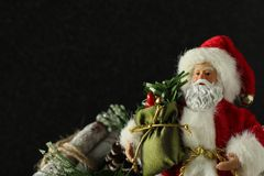 Santa Claus som rymmer en säck bredvid journalpacke på en svart bakgrund med att skriva utrymme arkivfoto