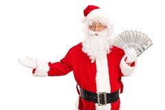 Santa Claus som rymmer en spridning av pengar Royaltyfria Foton