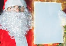 Santa Claus som rymmer en wishlist, en vit bokstav eller ett papper Royaltyfri Bild