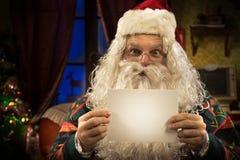 Santa Claus som rymmer ett tomt kort Arkivfoto