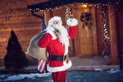 Santa Claus som rymmer hans påse och ringer en klocka det jul för ` s Arkivfoto