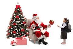 Santa Claus som sitter i en fåtölj bredvid en julgran och royaltyfri bild