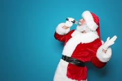 Santa Claus som sjunger in i mikrofonfärgbakgrund Julmusik royaltyfria foton