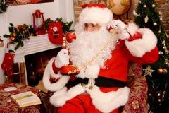 Santa Claus som stannar till tappningtelefonen arkivfoton
