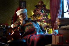 Santa Claus som ta sig en tupplur på hans fåtölj Arkivfoton