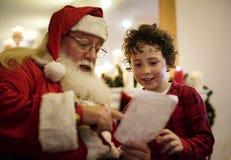 Santa Claus som talar med en pojke Arkivfoto