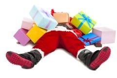 Santa Claus som tröttas för för att ligga på golv med många gåvaaskar Arkivbilder