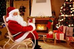 Santa Claus som tycker om och läser barn, önskar för x-mas Royaltyfri Foto