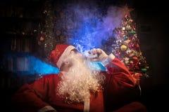 Santa Claus som vaping den elektroniska cigaretten som kläs som traditionell jultomten på en mörk tonad bakgrund med vapemoln Sel fotografering för bildbyråer