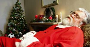 Santa Claus som vilar på soffan arkivfilmer