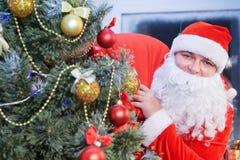Santa Claus sonriente con un saco en el suyo detrás Foto de archivo libre de regalías
