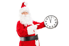 Santa Claus sonriente que señala en un reloj foto de archivo