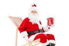 Santa Claus sonriente que se sienta en una silla y sostener de playa un regalo fotos de archivo