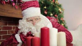 Santa Claus sopla hacia fuera las velas metrajes