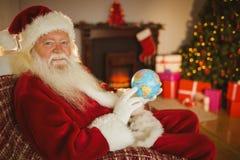 Santa Claus sorridente che tiene un globo Fotografia Stock Libera da Diritti