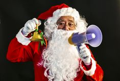 Santa Claus speaks on megaphone on his right hand & ring a bell on his lift hand studio shot on black background for family, givin. G, season, Christmas, holiday royalty free stock images