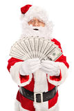Santa Claus spreading a stack of money Stock Image