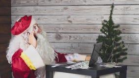 Santa Claus spreekt op een mobiele telefoon, werkt bij een computer, en gelddalingen aan hem stock footage