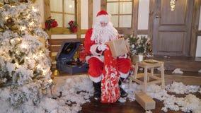 Santa Claus sta imballando i regali o i presente in borsa, si siede fuori della casa fra gli alberi di Natale, bevande mungono, a archivi video