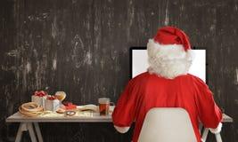 Santa Claus sta preparando per un viaggio e sta dividendo i regali sul computer Fotografie Stock Libere da Diritti