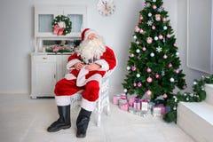 Santa Claus sta sedendosi in una sedia contro lo sfondo del immagine stock