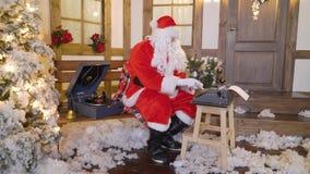 Santa Claus sta stampando la lettera dalla macchina da scrivere, si siede fuori della casa fra gli alberi di Natale, bevande mung video d archivio