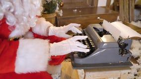 Santa Claus sta stampando la lettera dalla macchina da scrivere, si siede fuori della casa fra gli alberi di Natale, bevande mung stock footage