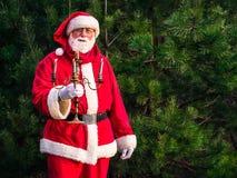 Santa Claus sta stando con un candeliere in un'abetaia Fotografia Stock
