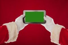 Santa Claus sta tenendo il piatto con un fondo verde Backgr rosso Immagini Stock