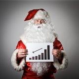 Santa Claus sta tenendo un diagramma in sue mani Immagine Stock Libera da Diritti