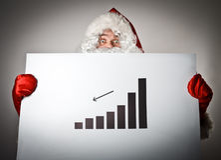 Santa Claus sta tenendo un diagramma in sue mani Fotografia Stock