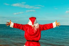 Santa Claus is standing on the beach with arms outstretched.