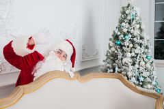 Santa Claus standing behind a Christmas tree and sofa looking at the camera.  Royalty Free Stock Photos