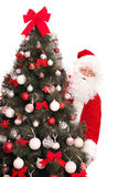 Santa Claus standing behind a Christmas tree Stock Image