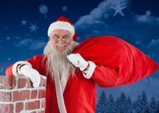 Santa claus standing besides chimney with his gift sack Royalty Free Stock Photos