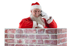Santa claus standing beside chimney and talking on mobile phone. Against white background stock photo