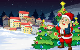 Santa Claus standing beside the Christmas trees near the village Royalty Free Stock Photo