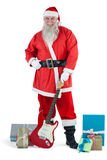 Santa claus standing with guitar and various gift Royalty Free Stock Image