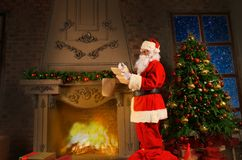 Santa Claus standing at his room at home near Christmas tree and big sack and reading Christmas letter or wish list. Stock Photos