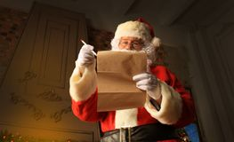 Santa Claus standing at his room at home near Christmas tree and big sack and reading Christmas letter or wish list. Santa Claus standing at his room at home Royalty Free Stock Images