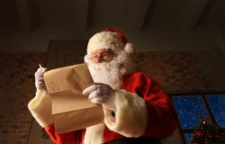 Santa Claus standing at his room at home near Christmas tree and big sack and reading Christmas letter or wish list. Santa Claus standing at his room at home Stock Photography