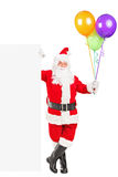 Santa claus standing next to a billboard. Full length portrait of a happy Santa claus standing next to a blank billboard and holding balloons on white Stock Photo